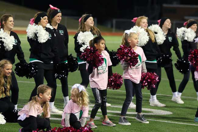 Elementary girls learn from the DCA Varsity Cheerleaders